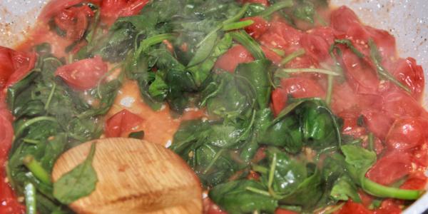 Spinat, Rucola und Tomate in Pfanne zubereitet